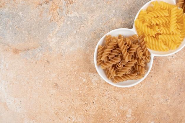 Deux types de macaronis non cuits sur plaque blanche.
