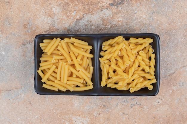 Deux types de macaronis non préparés sur plaque noire.