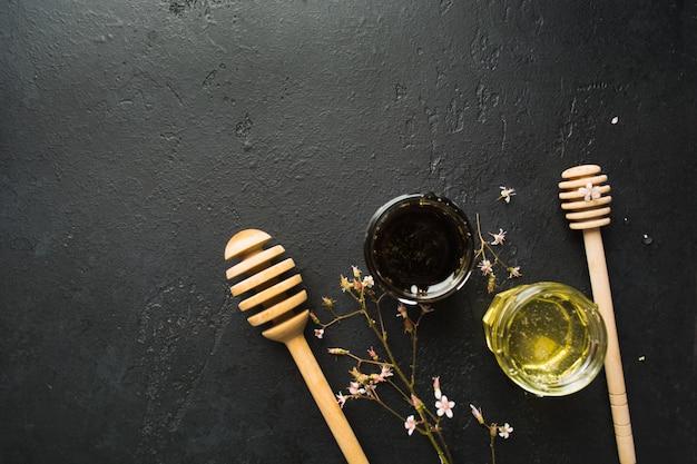 Deux types de miel bio naturel sain avec des cuillères et des petites fleurs