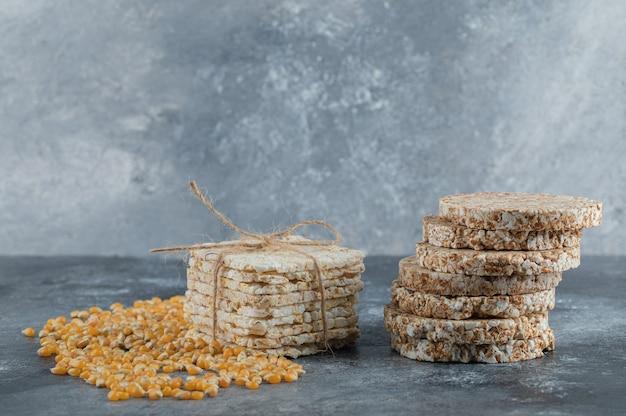 Deux types de pain croustillant et de graines de maïs crues sur marbre.