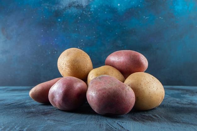 Deux types de pommes de terre biologiques placées sur une surface bleue.