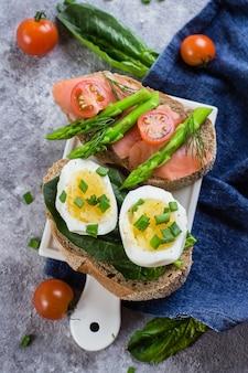 Deux types de sandwich aux épinards, œufs à la coque et saumon salé, tomates cerises, asperges vertes