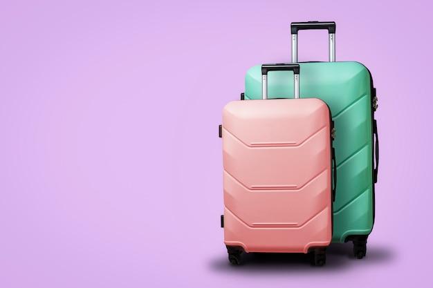 Deux valises sur roues sur fond violet. concept de voyage, un voyage de vacances, une visite à des proches. couleur rose et verte