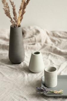 Deux vases blancs, petit plateau en céramique grise avec bouquet de lavande sèche et cruche noire avec plante debout en ligne sur table recouverte de toile de lin