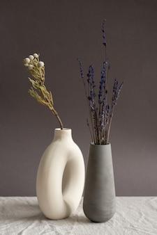 Deux vases en céramique faits à la main de couleur blanche et noire avec des fleurs sauvages séchées à l'intérieur debout près de l'autre sur une table recouverte de tissu