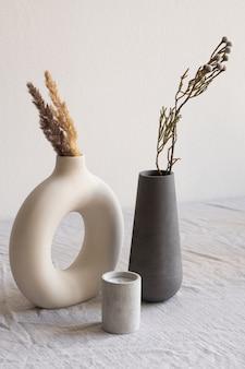 Deux vases faits à la main en céramique avec des fleurs sauvages séchées et des pointes et bougie aromatique debout sur une table recouverte de tissu de lin blanc