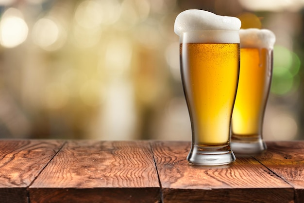 Deux verre de bière avec de la mousse sur une table en bois brun vide