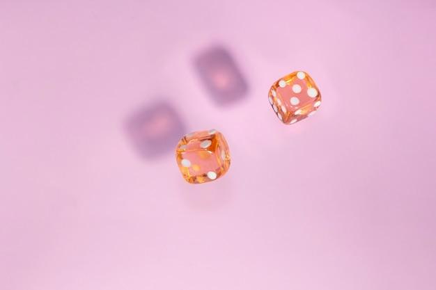 Deux dés en verre tombent, os à gibier sur fond rose.