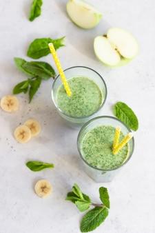 Deux verres aux épinards verts, banane, pomme et menthe smoothie à la paille jaune