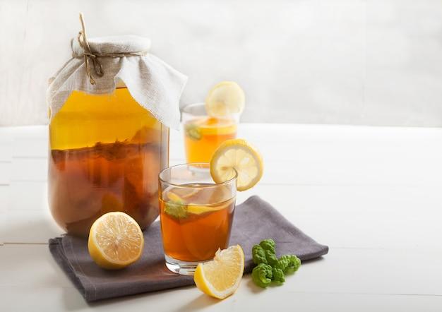Deux verres et banque avec kombucha et tranches de citron sur un tableau blanc