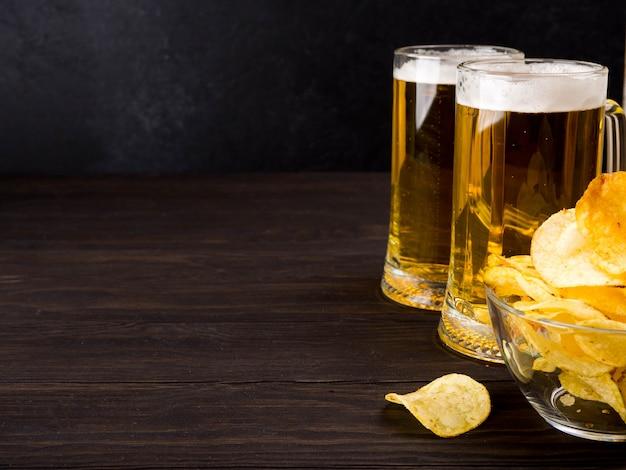 Deux verres de bière et chips sur fond sombre en bois, espace copie