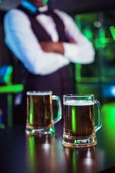 Deux verres de bière sur le comptoir et le barman