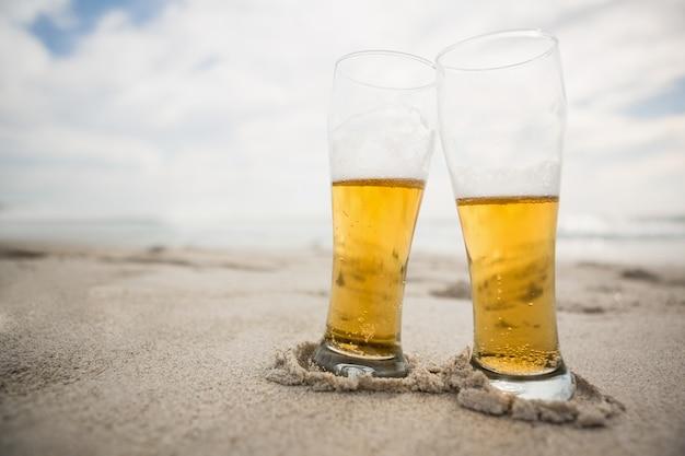 Deux verres de bière conservés sur le sable