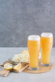 Deux verres de bière avec du fromage et des tranches de citron sur gris.