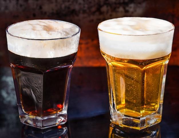 Deux verres de bière foncée et légère fraîchement versée sur une surface miroir noire. concept de nourriture et de boissons