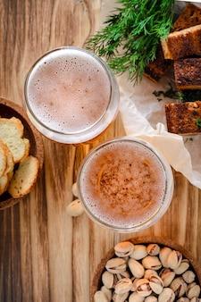 Deux verres de bière légère et des collations, des pistaches et des croûtons sur une table en bois