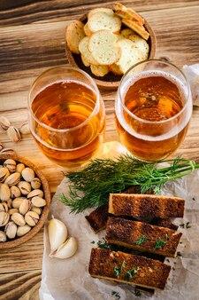 Deux verres de bière légère, pistaches et croûtons sur une table en bois.