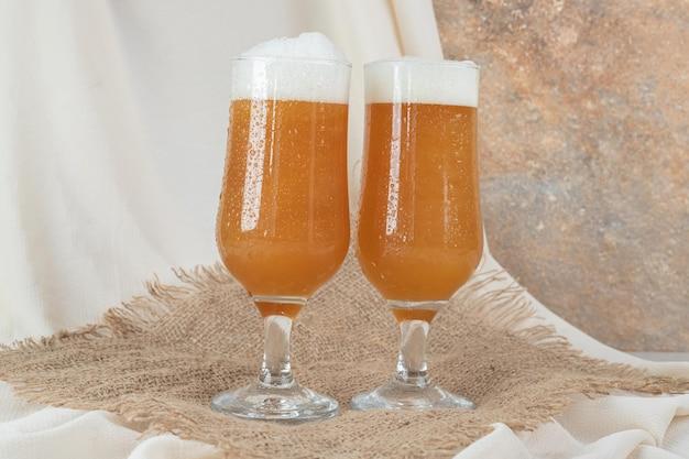 Deux verres de bière mousseuse sur toile de jute