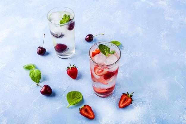 Deux verres de boisson fraîche rafraîchissante avec fraise, cerise et menthe sur table bleue. diverses limonades d'été ou thé glacé. cocktails mojito avec des glaçons.
