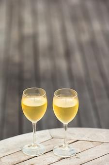 Deux verres de bon vin blanc au coucher du soleil sur une table en bois
