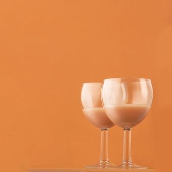 Deux verres de café deux verres de liqueur de café sur fond marron, photo carrée. copiez la liqueur spaceee sur fond marron, photo carrée. copier l'espace.
