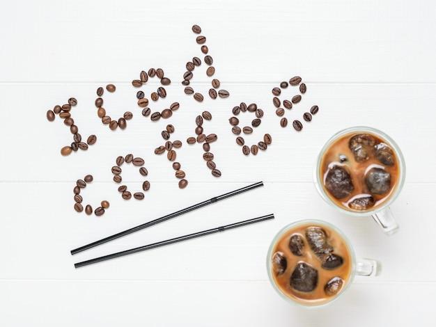Deux verres de café glacé, deux tubes à cocktail et une inscription de café glacé sur une table blanche. boisson rafraîchissante et revigorante de grains de café et de lait. la vue du haut. mise à plat.