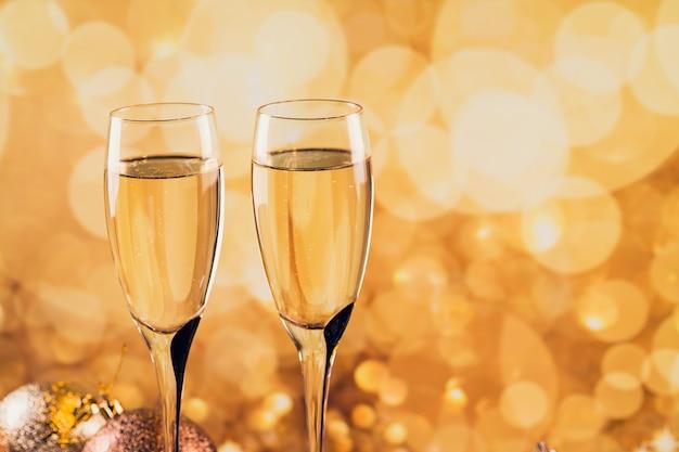 Deux verres de champagne avec bokeh léger doré sur fond. dîner romantique. concept de vacances d'hiver.