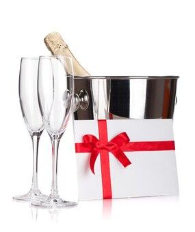 Deux verres de champagne, une bouteille dans un seau et une lettre. isolé sur fond blanc