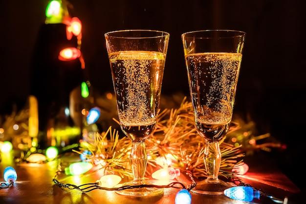 Deux verres de champagne et une bouteille sur une table en bois décorée d'accessoires de noël pour célébrer le nouvel an et noël. soirée romantique. la lueur des guirlandes. la saint-valentin