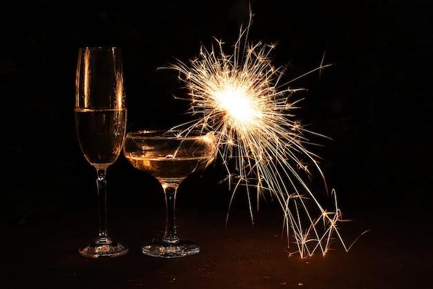 Deux verres de champagne avec des cierges magiques sur fond sombre, vacances et concept de noël.