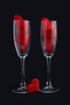 Deux verres à champagne avec des coeurs rouges sur fond noir. joyeux dîner de la saint-valentin. 14 février. verticale