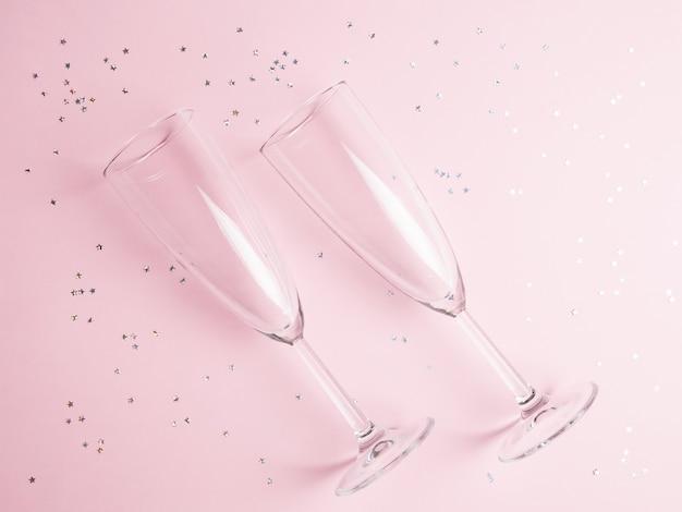 Deux verres de champagne avec des confettis. mise à plat, vue de dessus,