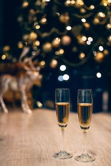 Deux verres de champagne debout sur l'arbre de noël décoré flou.