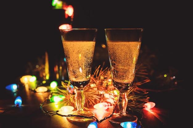 Deux verres de champagne et décorations de noël. soirée romantique avec consommation d'alcool. la célébration du nouvel an et de noël. joyeuses vacances.
