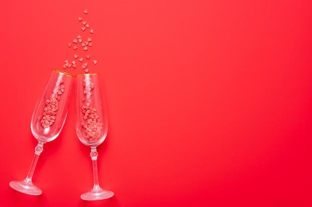 Deux verres de champagne avec des éclaboussures de confettis coeur rouge