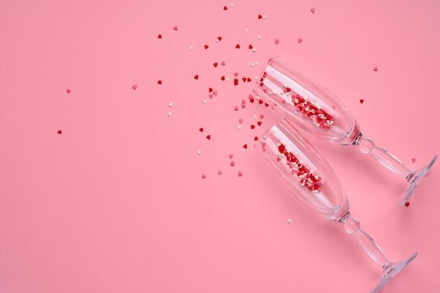 Deux verres à champagne avec des éclaboussures de confettis en forme de coeur rouge sur une table rose. concept de la saint-valentin. vue de dessus, copiez l'espace.