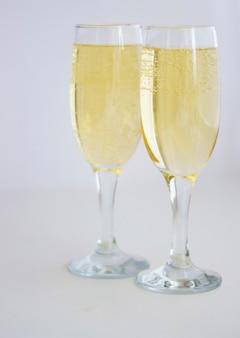 Deux verres de champagne sur fond blanc.