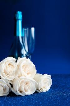 Deux verres de champagne froid et un bouquet de roses blanches sur fond bleu classique. saint valentin
