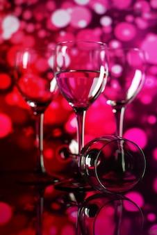 Deux verres de champagne avec des lumières en arrière-plan. profondeur de champ très faible, focalisation sur le verre proche.