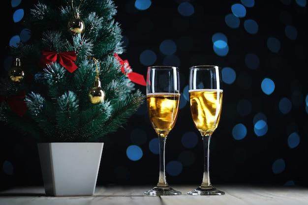 Deux verres de champagne et petit arbre de noël sombre fond de lumières.