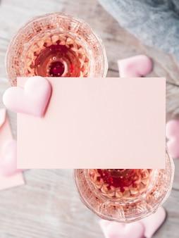 Deux verres de champagne à pied avec carte de note en papier vierge coeurs roses à remplir avec votre texte sur bois texturé.