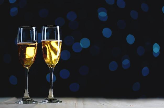 Deux verres de champagne sombre luminescent fond. espace de copie