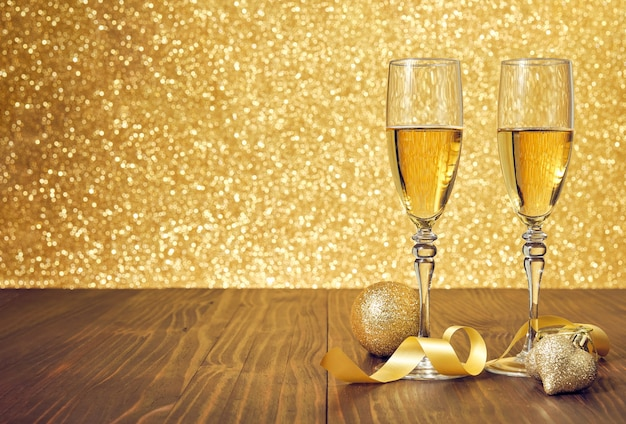 Deux verres de champagne sur une table en bois marron avec des décorations de noël et un fond or flou
