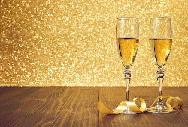 Deux verres de champagne sur une table en bois marron sur fond doré brillant