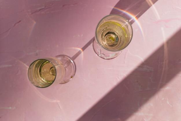 Deux verres de champagne sur une table rose