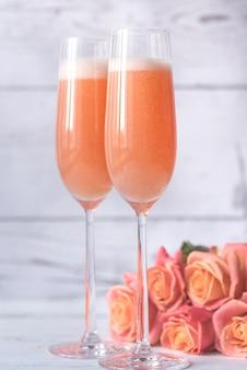 Deux verres de cocktail bellini avec bouquet de roses