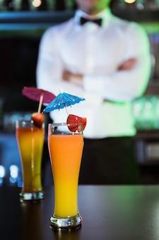 Deux verres de cocktail sur le comptoir et le barman