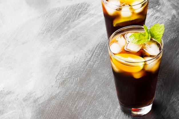 Deux verres de cocktail cuba libre sur un fond sombre. espace de copie. fond de nourriture