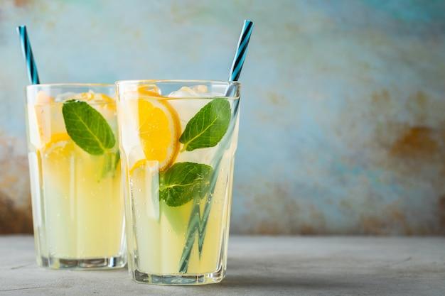 Deux verres avec un cocktail de limonade ou de mojito.