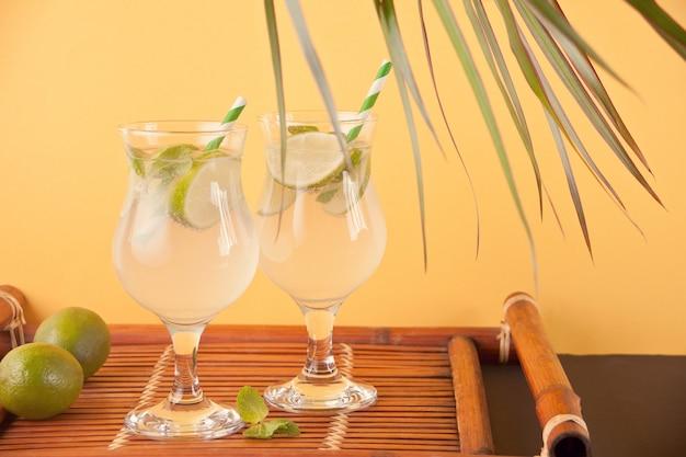 Deux verres avec cocktail mojito sur le fond orange.